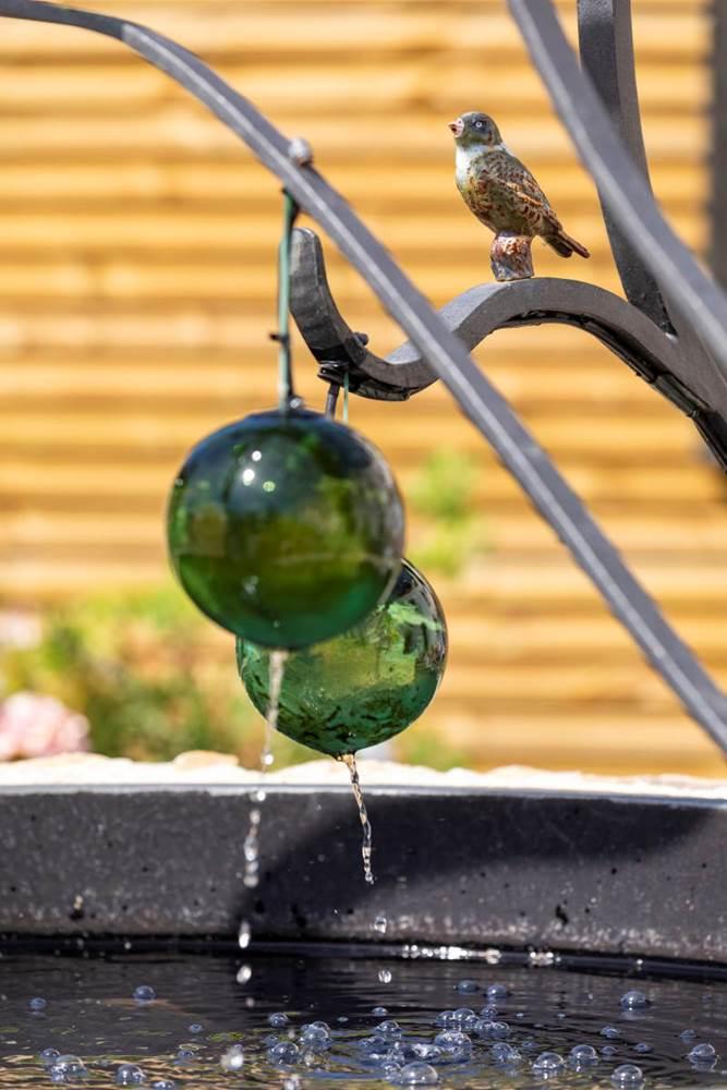 Les boules de verre comme en suspension, laisse s'écouler l'eau de la fontaine ©